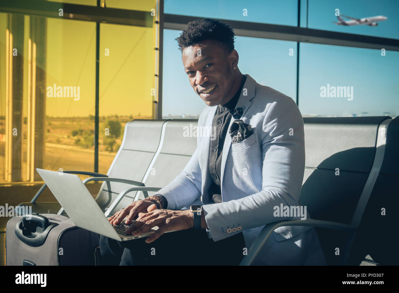 One young and attractive black businessman is seated in the airport terminal working with a laptop, and smiling. He is carrying a suitcase and wearing - Stock Image