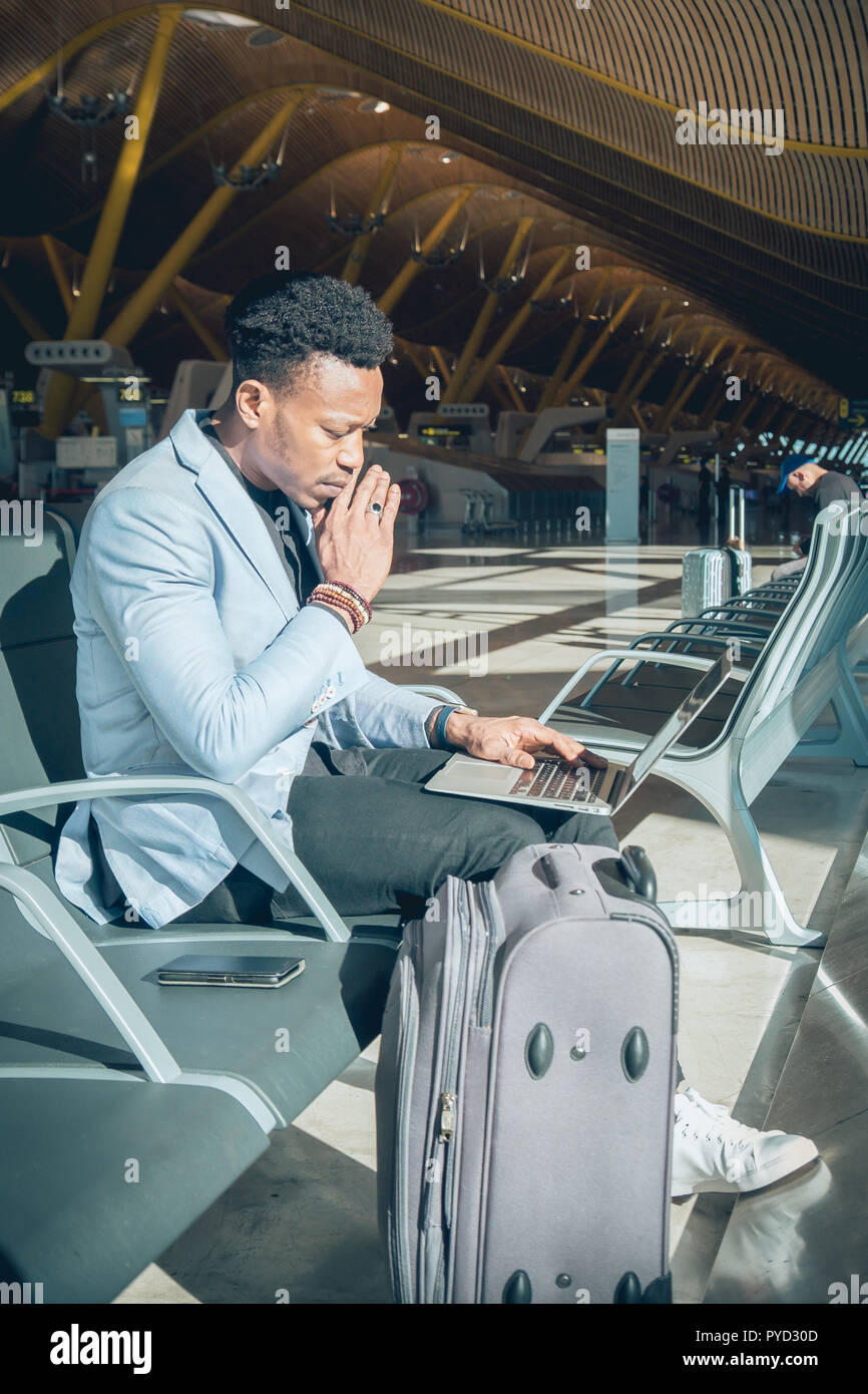 One young and attractive black businessman is seated in the airport terminal working with a laptop near de chack-in desks. He is carrying a suitcase a - Stock Image