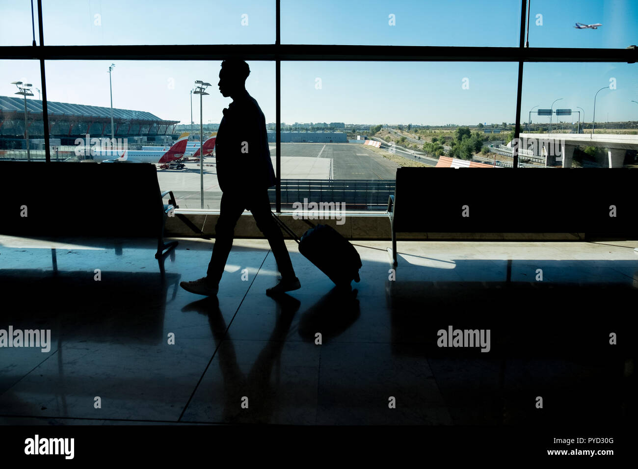 One young businessman is walking through the airport carrying a suitcase in front of the window with aeroplanes waiting in the fingers behind the glas - Stock Image