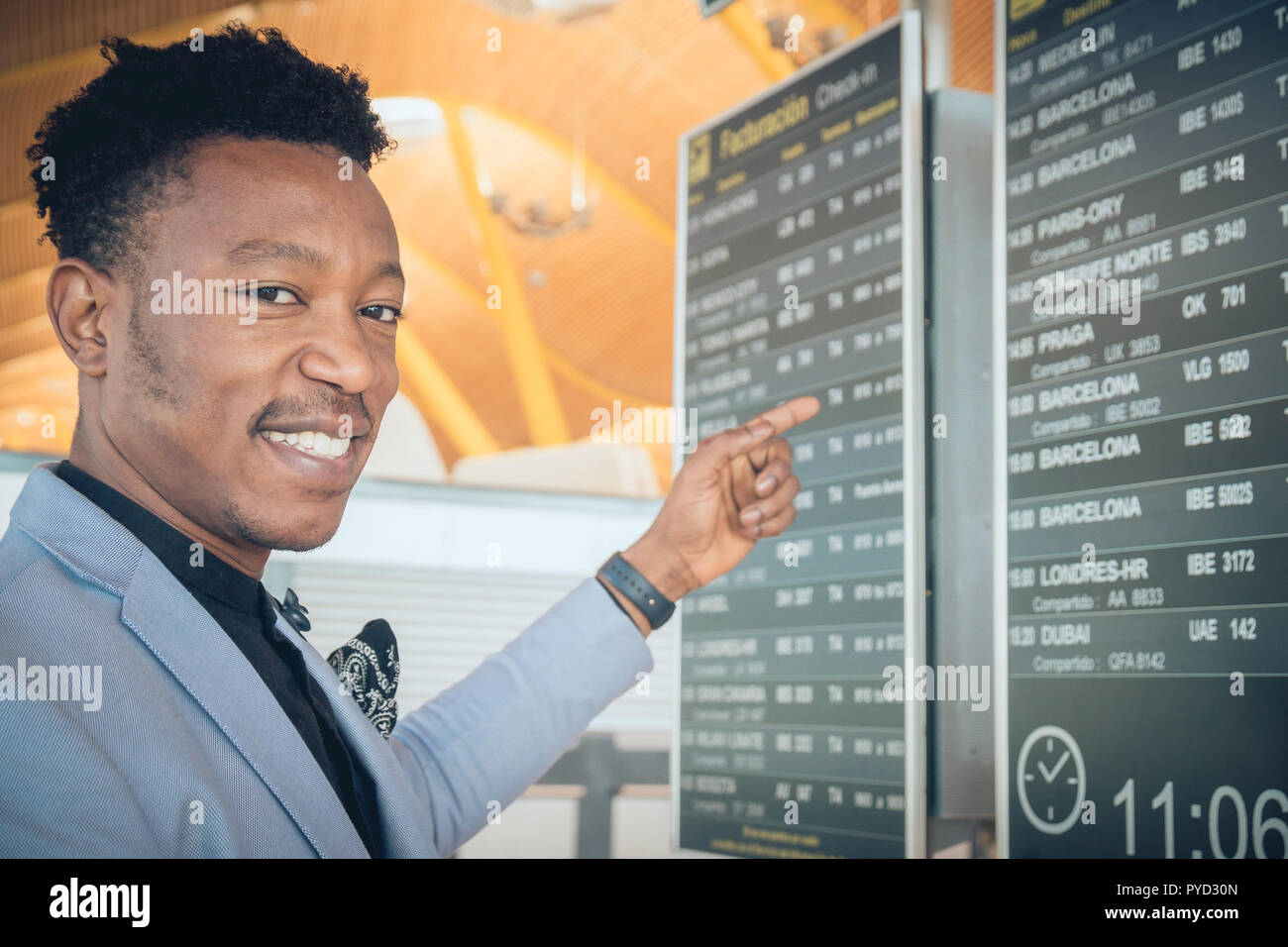 One young and attractive black businessman is looking for his flight to Barcelona in the airport terminal near check-in screens. He is wearing formal  - Stock Image