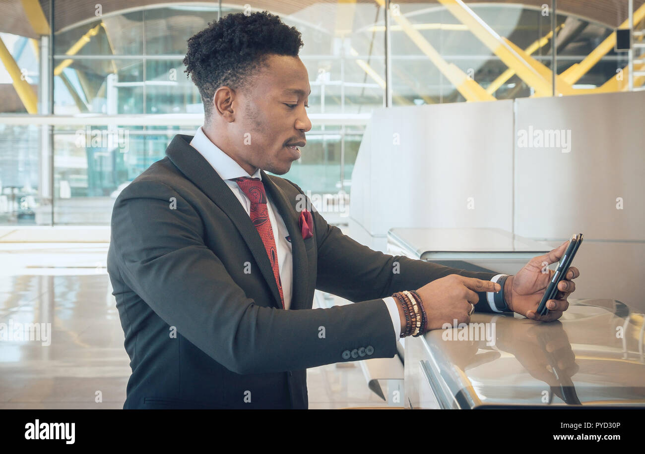 Close up pf one young and attractive black businessman looking for his mobile telephone on the check-in desks in the airport. He is wearing a black su - Stock Image