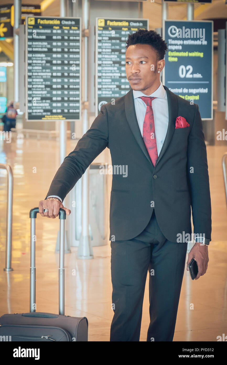 One young and attractive black businessman is walking in the airport terminal near the check-in desks . He is carrying a suitcase and wearing a black  - Stock Image