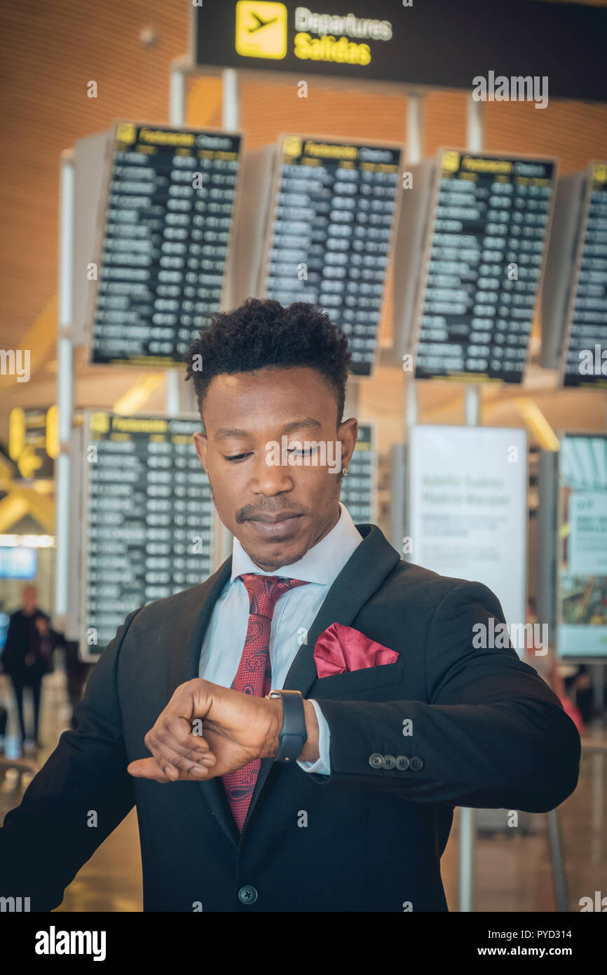 Close up of one young and attractive black businessman is looking at his smart watch in the airport terminal in front of the departures information di - Stock Image