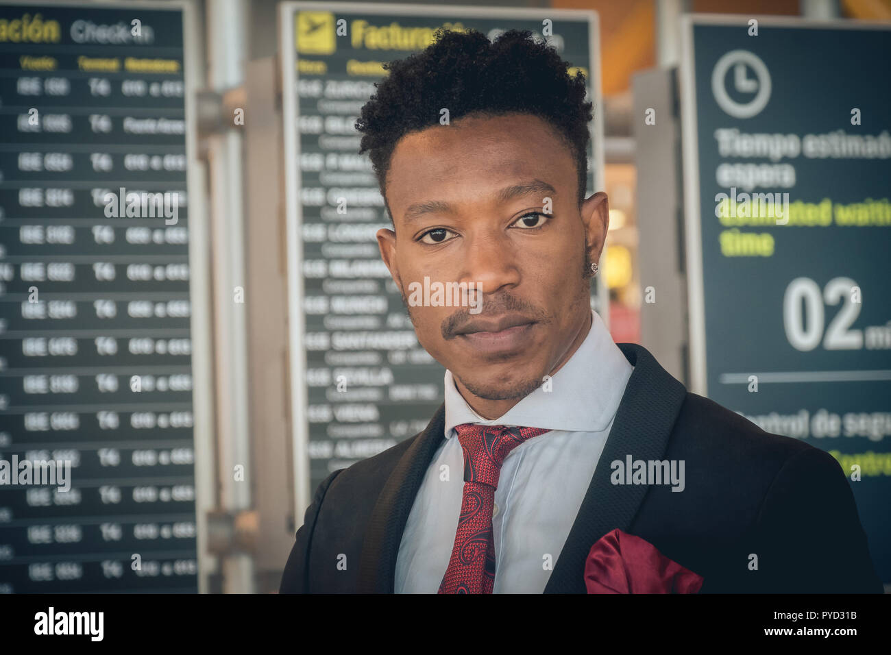 Close up of one young and attractive black businessman smiling in the airport terminal in front of the departures information displays. He is wearing  - Stock Image