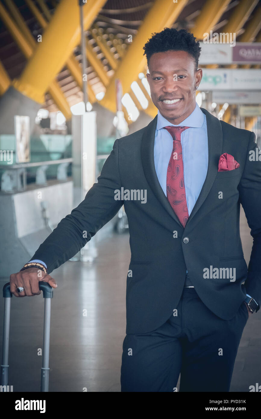 Close uo of one young and attractive black businessman is waiting for a car outside of the airport wearing a black suit with a red tie and carrying a  - Stock Image