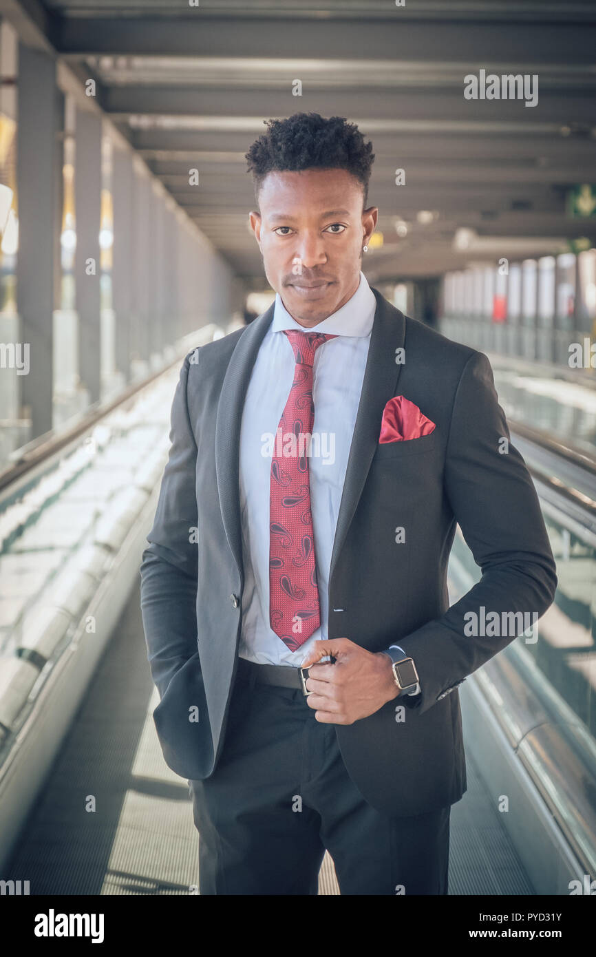 Close up of one young and attractive black businessman looking at the camera while he is waiting for a car outside of the airport wearing a black suit - Stock Image