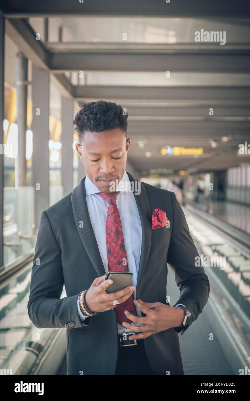 Close up of one young and attractive businessman going to the airport looking at his smartwatch to be on time. He is wearing a black suit with a red t - Stock Image