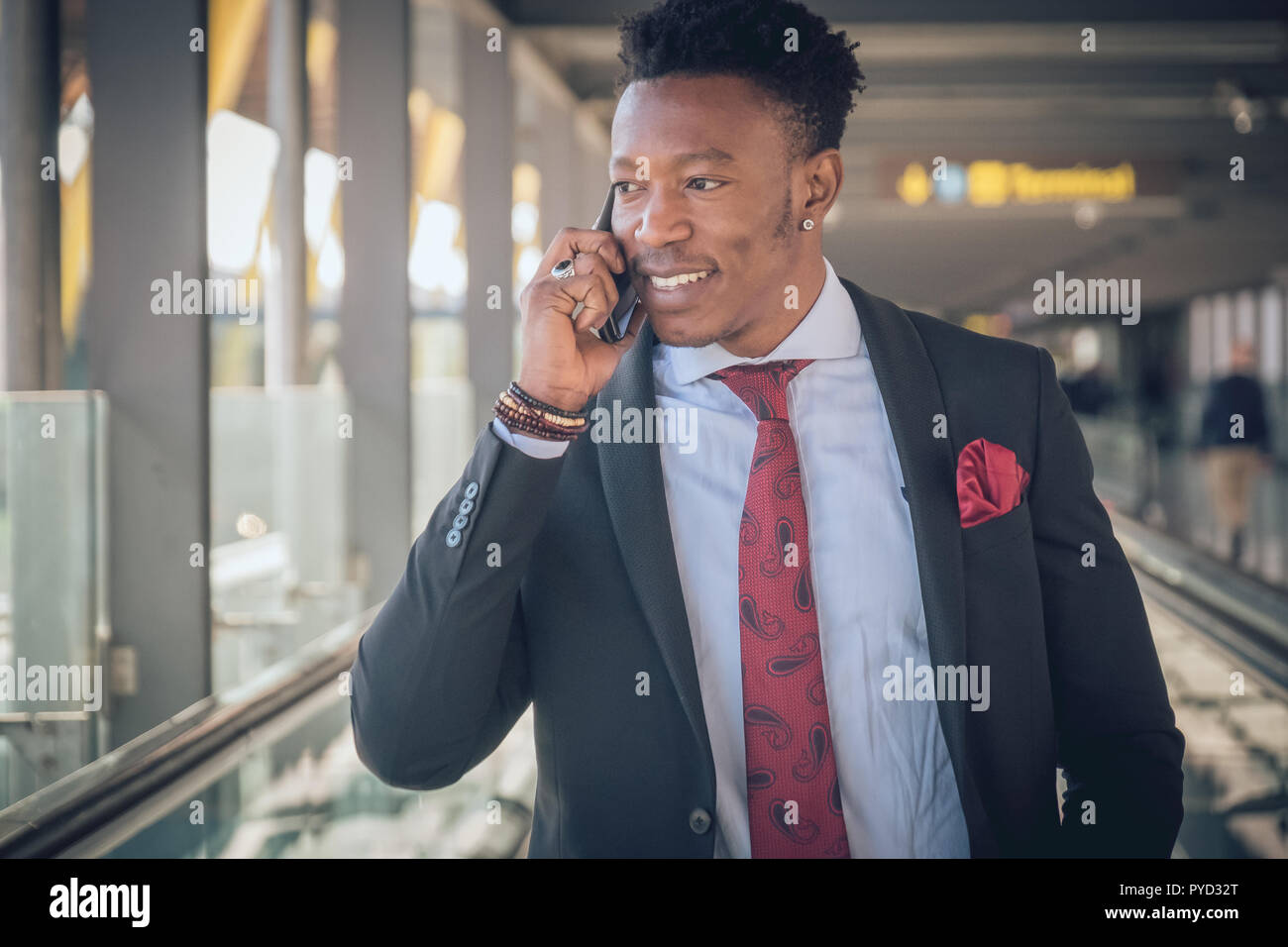 Close up of one young and attractive black businessman going to the airport wearing a black suit with a red tie. He is smiling and talking by telephon - Stock Image