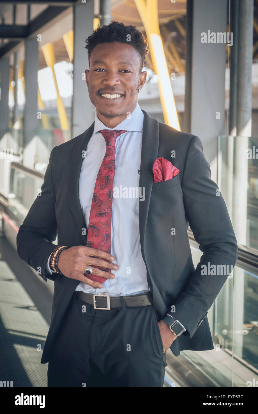 Close up of one young and attractive black businessman looking at the camera and smiling outside of the airport wearing a black suit with a red tie - Stock Image