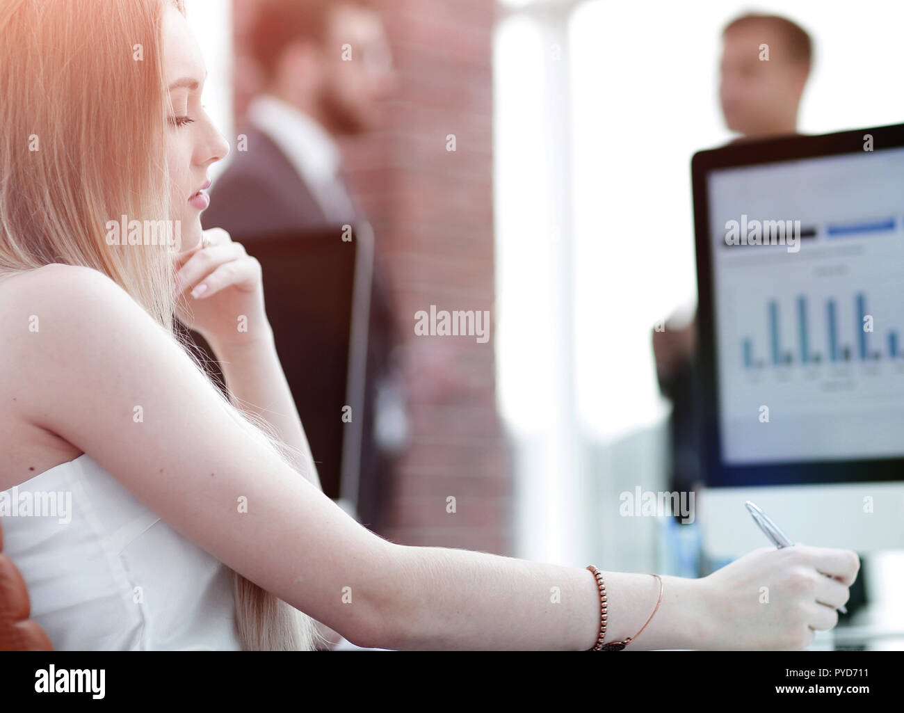 Business woman working in office with business graph on computer - Stock Image
