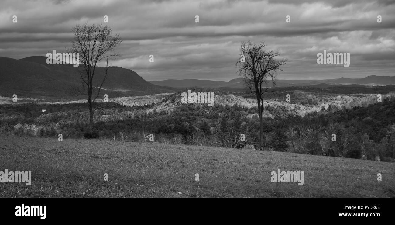 Black and white landscape of Berkshire Hills, Mass with sunlight breaking through clouds onto fall foliage - Stock Image