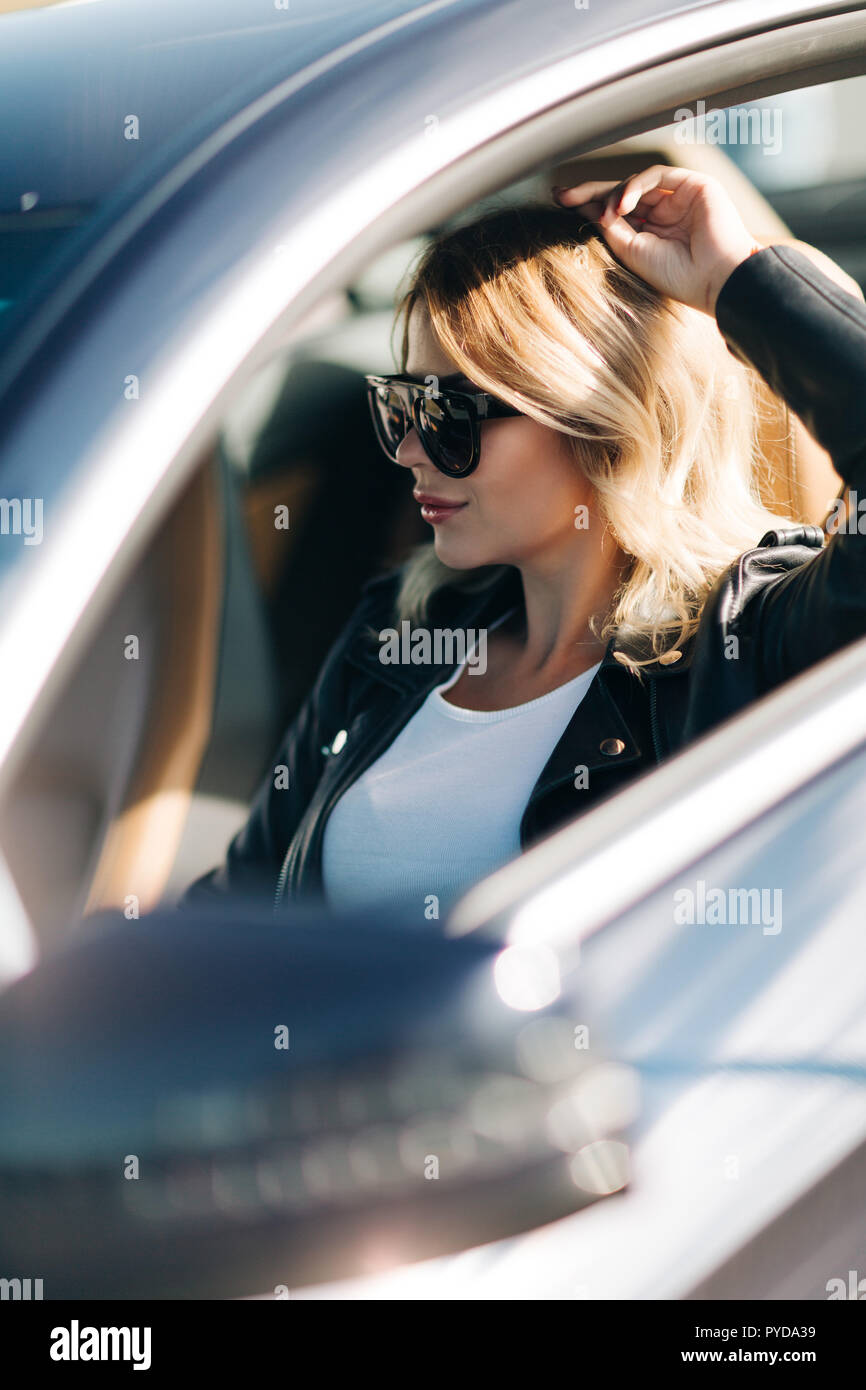 Picture of woman on sunglasses sitting in car. Focussing on girl. - Stock Image