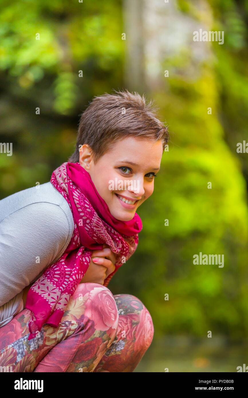 Short-haired teen girl isolated in nature - Stock Image
