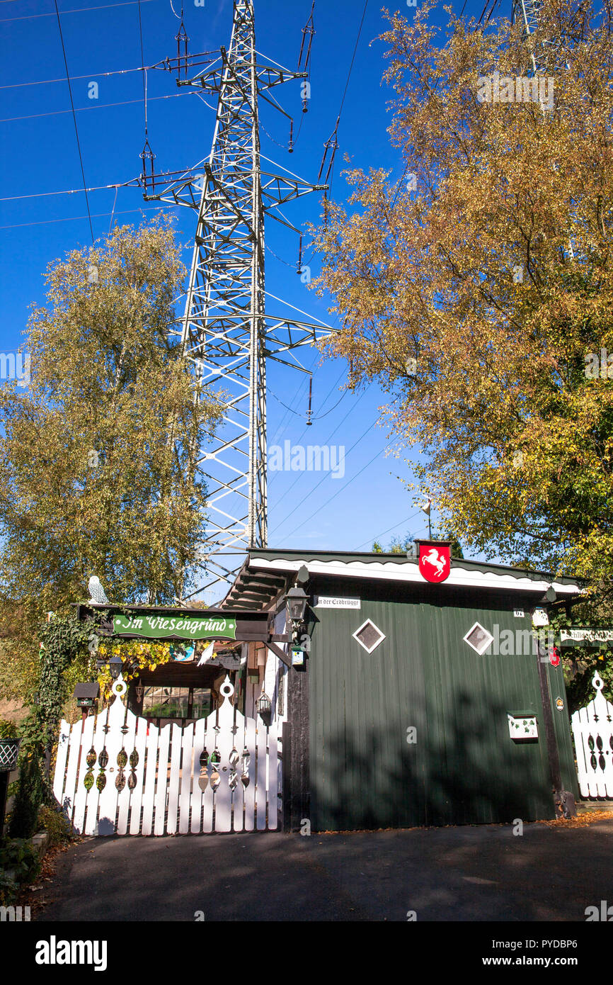 allotment hut under a high voltage pylon in Herdecke, Germany.  Schrebergarten-Haeuschen unter einem Hochspannungsmast in Herdecke, Deutschland. - Stock Image
