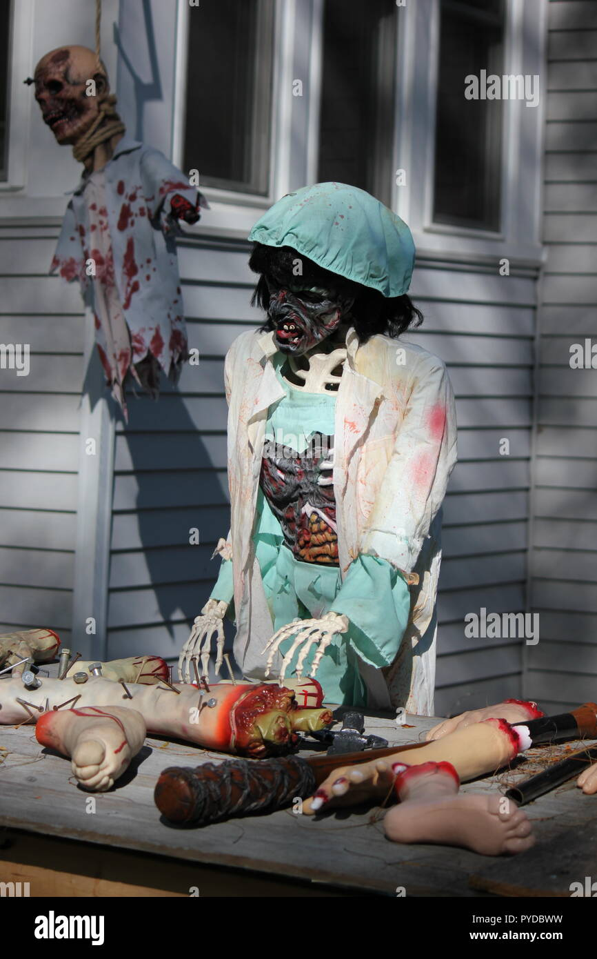 Woman doctor monster examining human body parts legs and arms as creative Halloween lawn decorations. - Stock Image