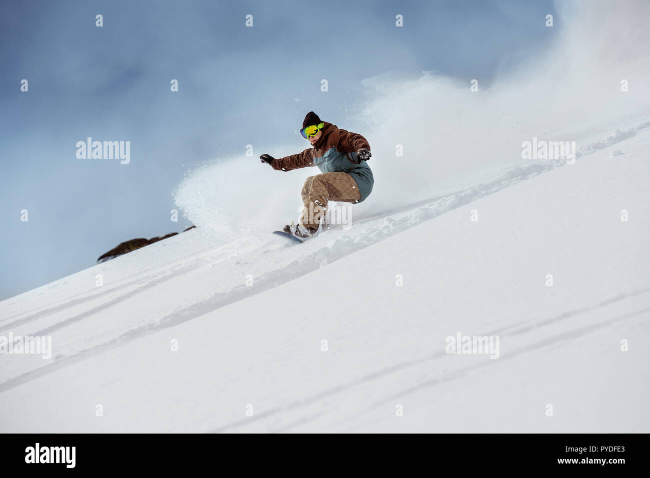 Snowboarder downhill at offpiste slope. Freeride or backcountry snowboarding concept - Stock Image