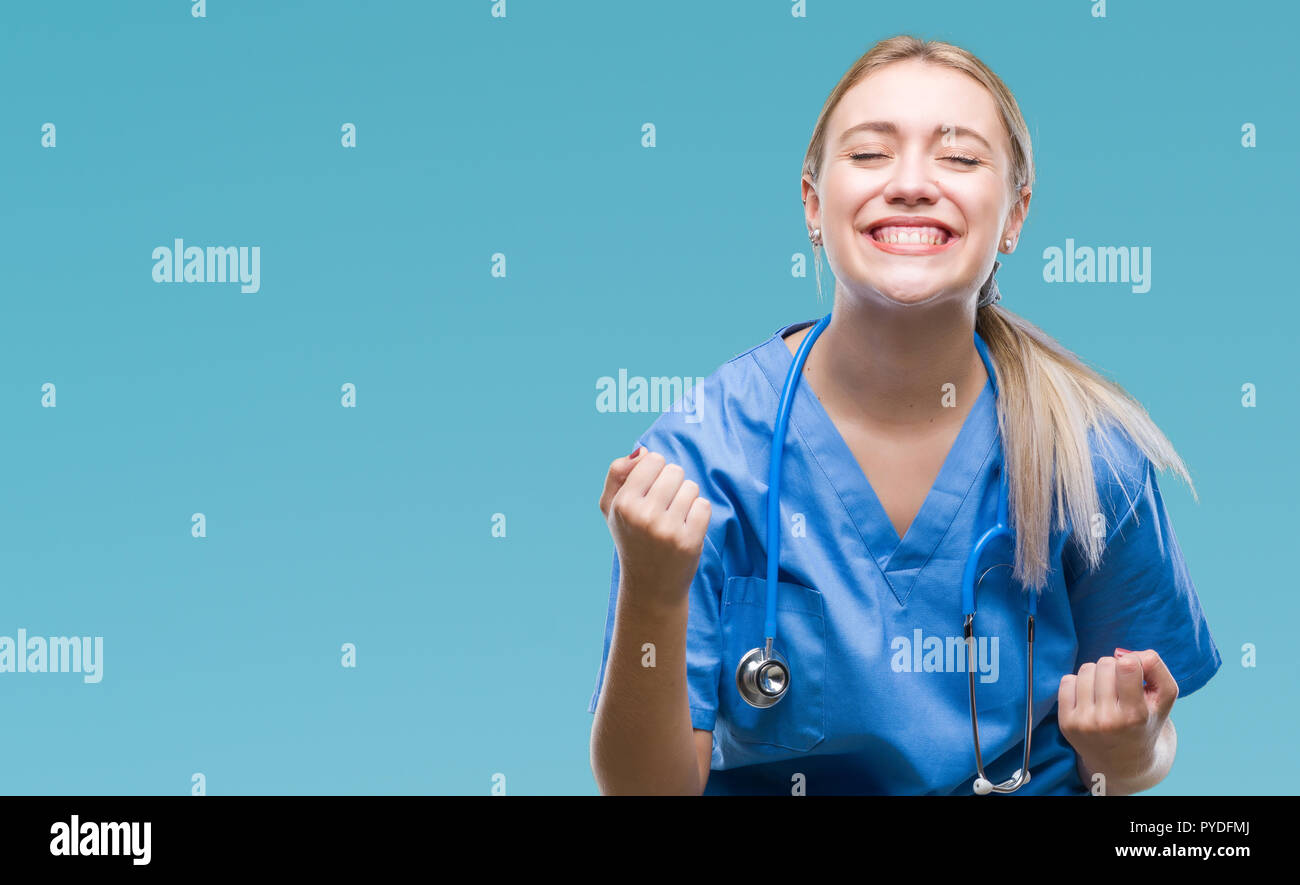 Young blonde surgeon doctor woman over isolated background very happy and excited doing winner gesture with arms raised, smiling and screaming for suc Stock Photo