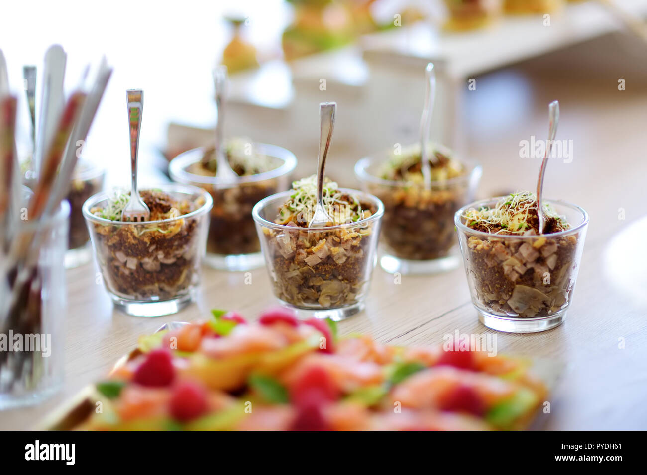 Fresh and delicious vegetable and pork salad served in mini glasses on a party or wedding reception. Plates with assorted fancy finger food snacks on  Stock Photo
