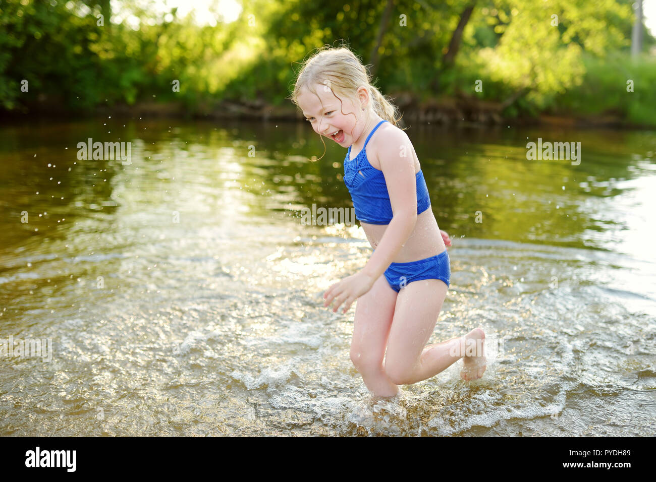 2609d91e6722 Cute little girl wearing swimsuit playing by a river on hot summer day.  Adorable child having fun outdoors during summer vacations. Water  activities f