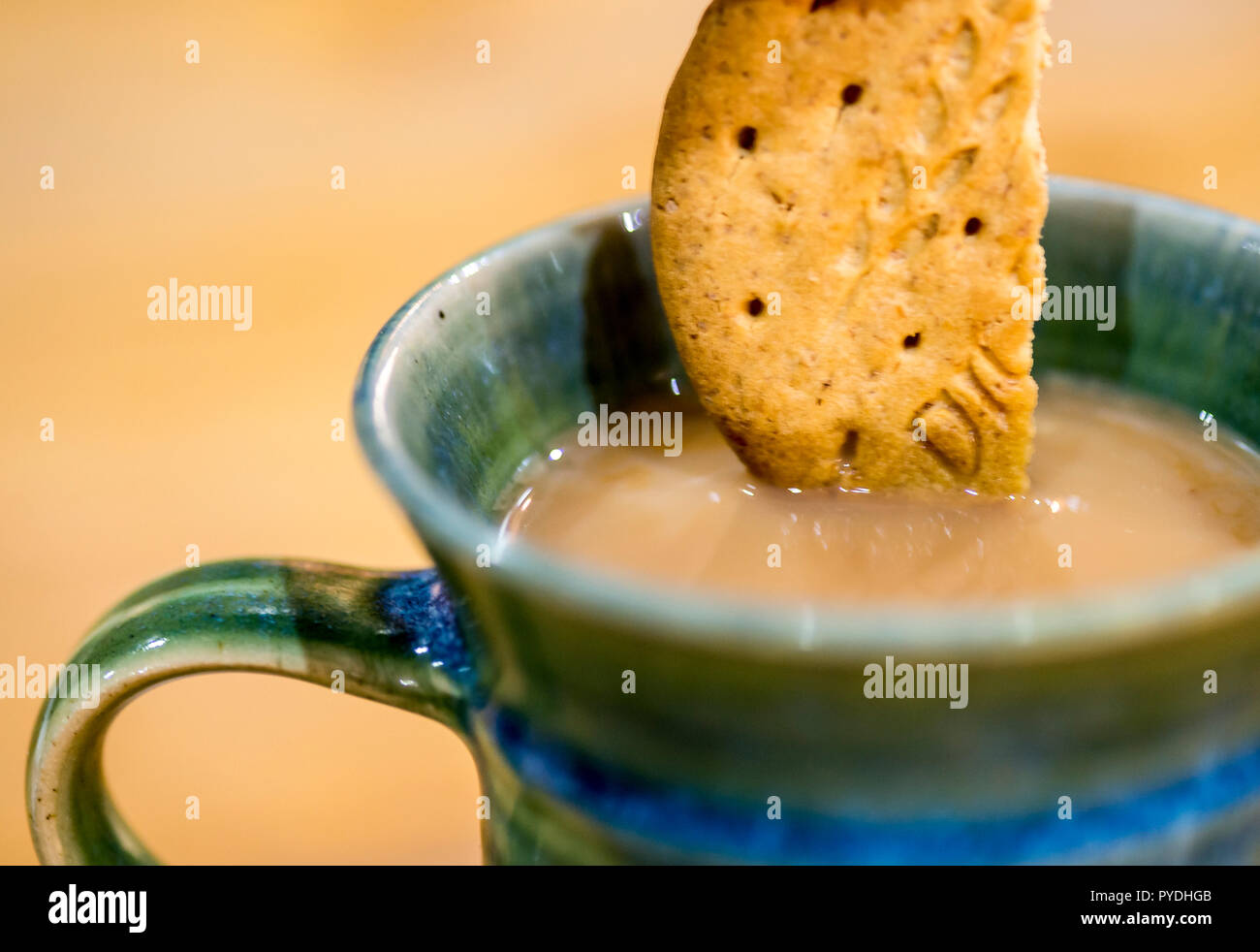 Digestive biscuit dipped in a cup of tea. - Stock Image