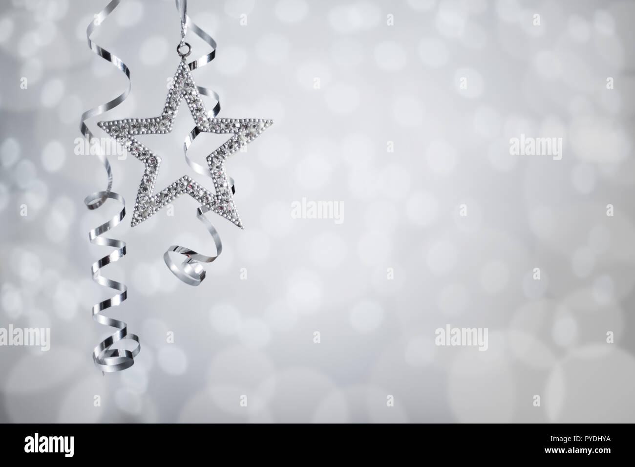 silver christmas new year curly streamer ribbon and star over glittering bokeh lights background with copy space for text