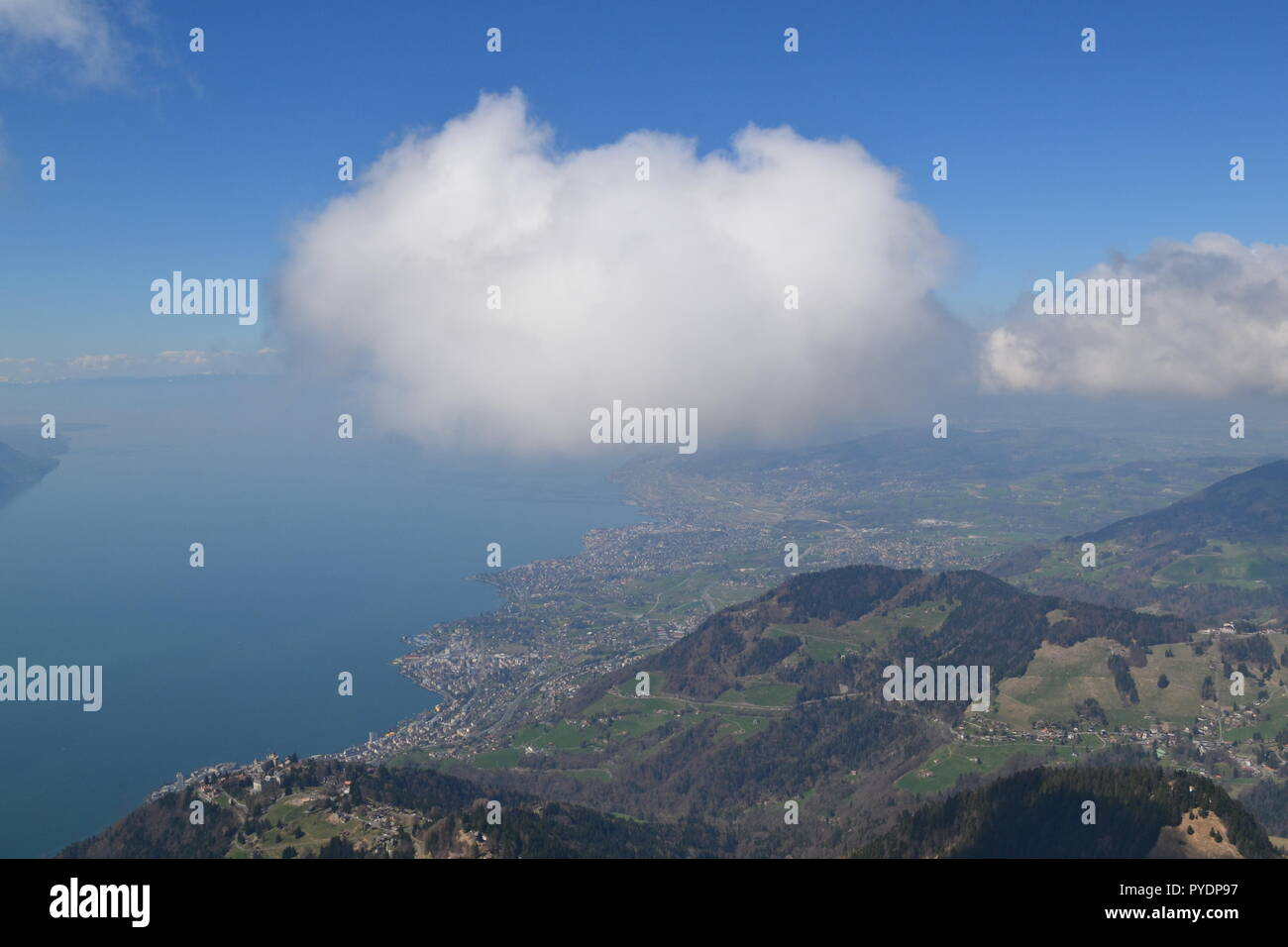 View from Les Rochers de Naye, reached by MOB train from Montreux. To west is Lake Geneva, Lausanne. A cumulus cloud floats past. - Stock Image