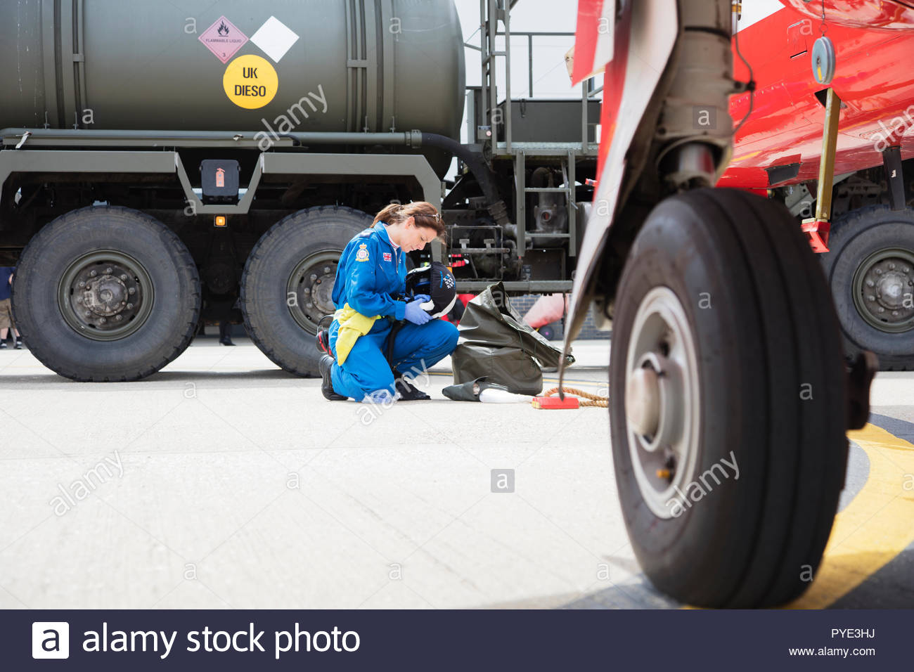 Crouched Red Arrows pilot holding helmet on RAF Scrampton, UK Stock Photo