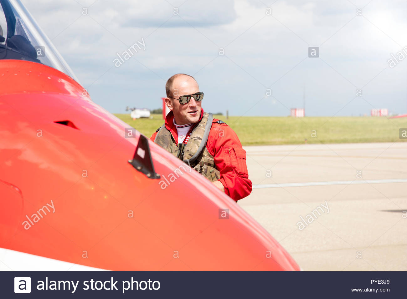 Red Arrows pilot wearing sunglasses by airplane on RAF Scrampton, UK - Stock Image