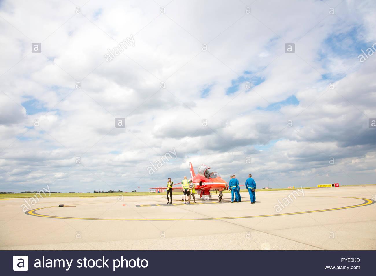 People by Red Arrows airplane on RAF Scrampton, UK - Stock Image