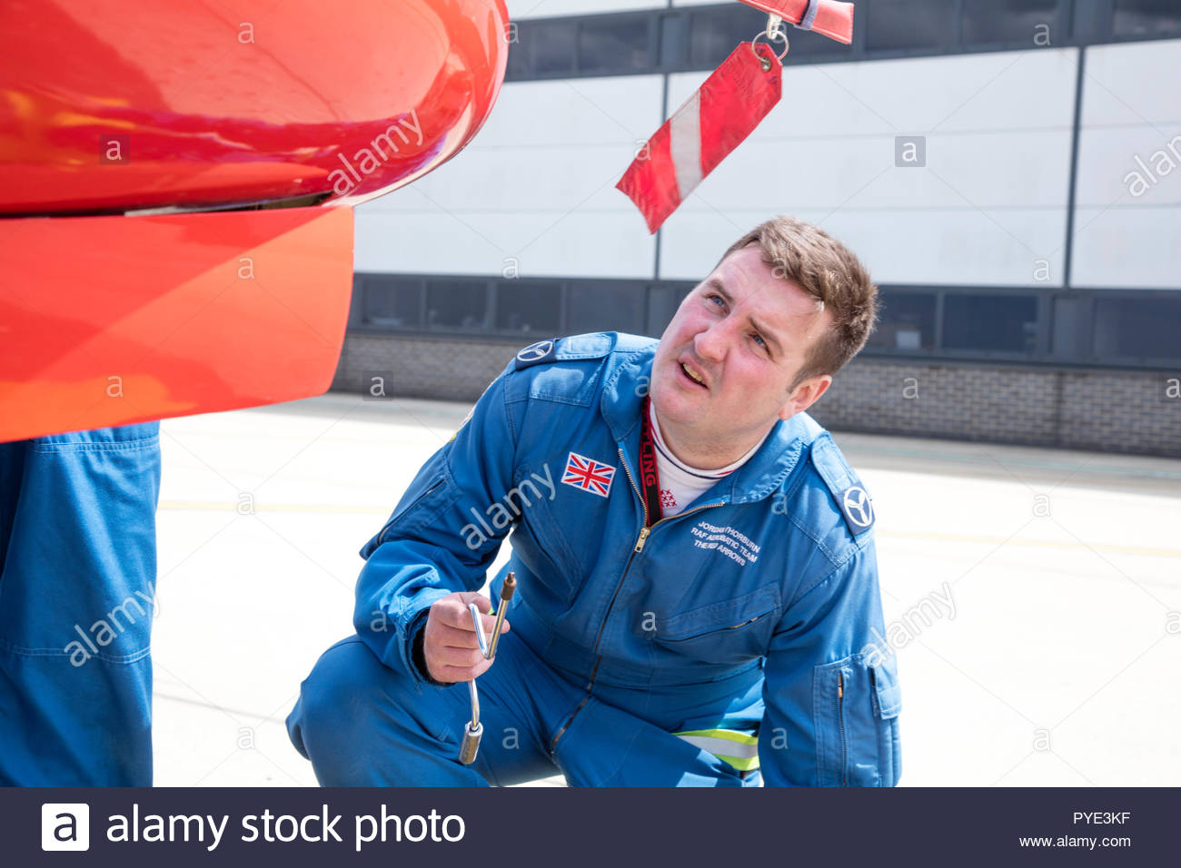 Man holding tool crouched by Red Arrows airplane on RAF Scrampton, UK - Stock Image