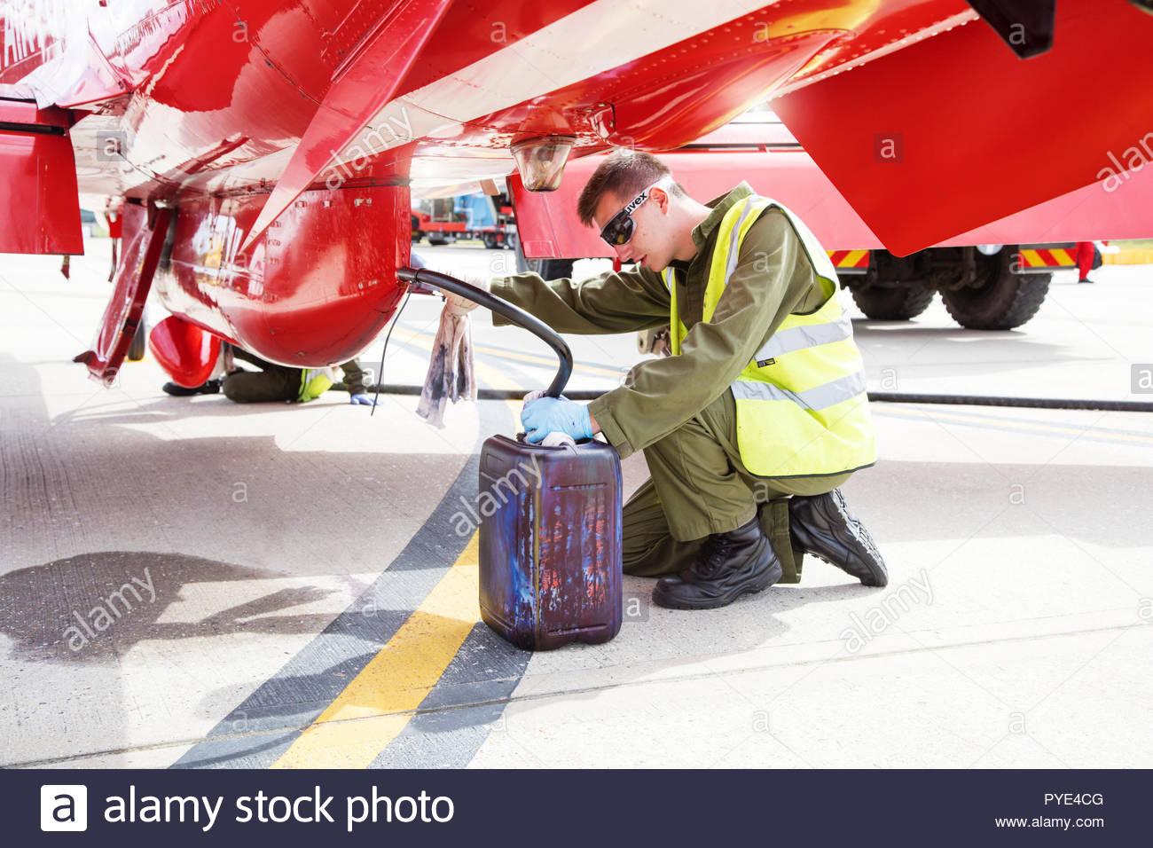 Man draining Red Arrows airplane on RAF Scrampton, UK - Stock Image