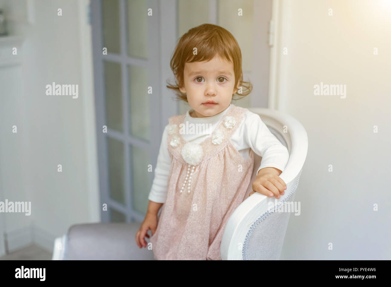 9adc1116986d Sweet little girl in pastel pink dress at home sitting on modern ...