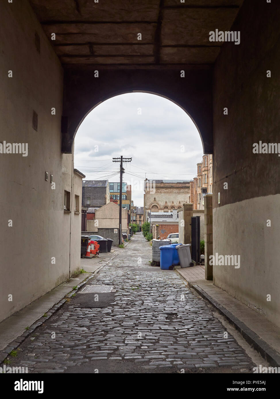 Looking down an Old Passageway with a cobbled road surface on a Cloudy Summers day in Glasgow, Scotland, UK. - Stock Image