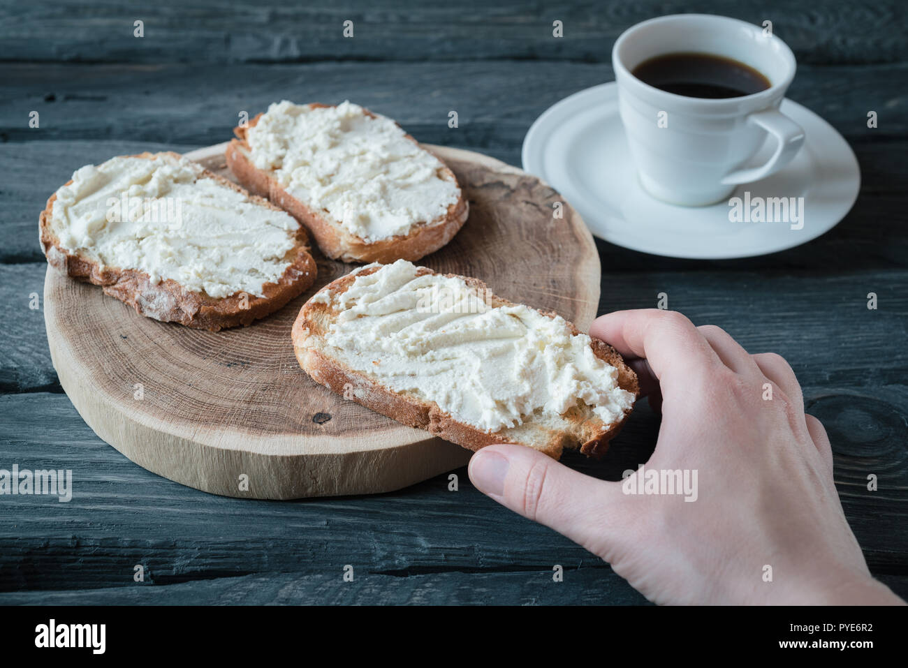 Hand holds homemade sandwiche with cream-cheese over a black wooden table. Wooden stand with sandwiches. Breakfast with black coffee. - Stock Image