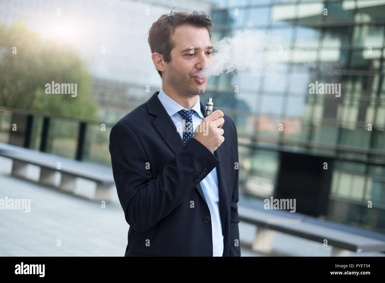 Businessman vaping with his electronic cigarette - Stock Image