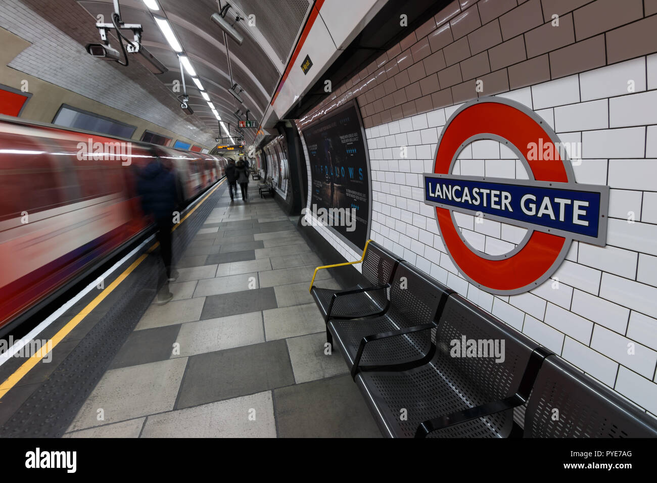 London Underground sign with moving train and people at Lancaster Gate station  LONDON - MARCH 07, 2015: London Underground sign with moving train and Stock Photo