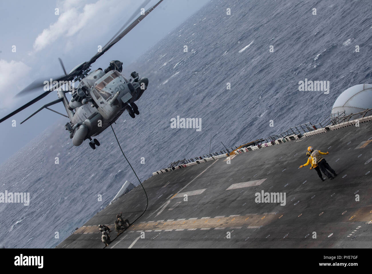 A CH-53E Super Stallion with Marine Medium Tiltrotor Squadron 264 (Reinforced), 22nd Marine Expeditionary Unit, hovers above the flight deck while conducting fast rope training during the Carrier Strike Group 4 Composite Training Unit Exercise (COMPTUEX) aboard the Wasp-class amphibious assault ship USS Kearsarge (LHD 3), Oct. 25, 2018. COMPTUEX is the final pre-deployment exercise that certifies the combined Kearsarge Amphibious Ready Group and 22nd MEU's abilities to conduct military operations at sea and project power ashore through joint planning and execution of challenging and realistic  - Stock Image
