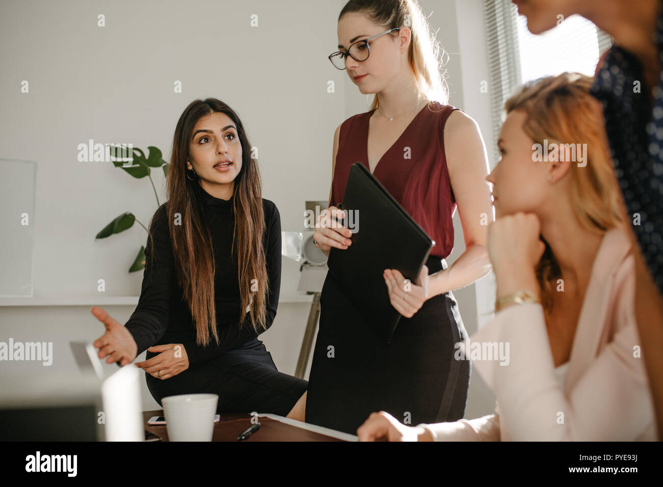 Young Woman Sharing Her Ideas With Colleagues In Office Group Of