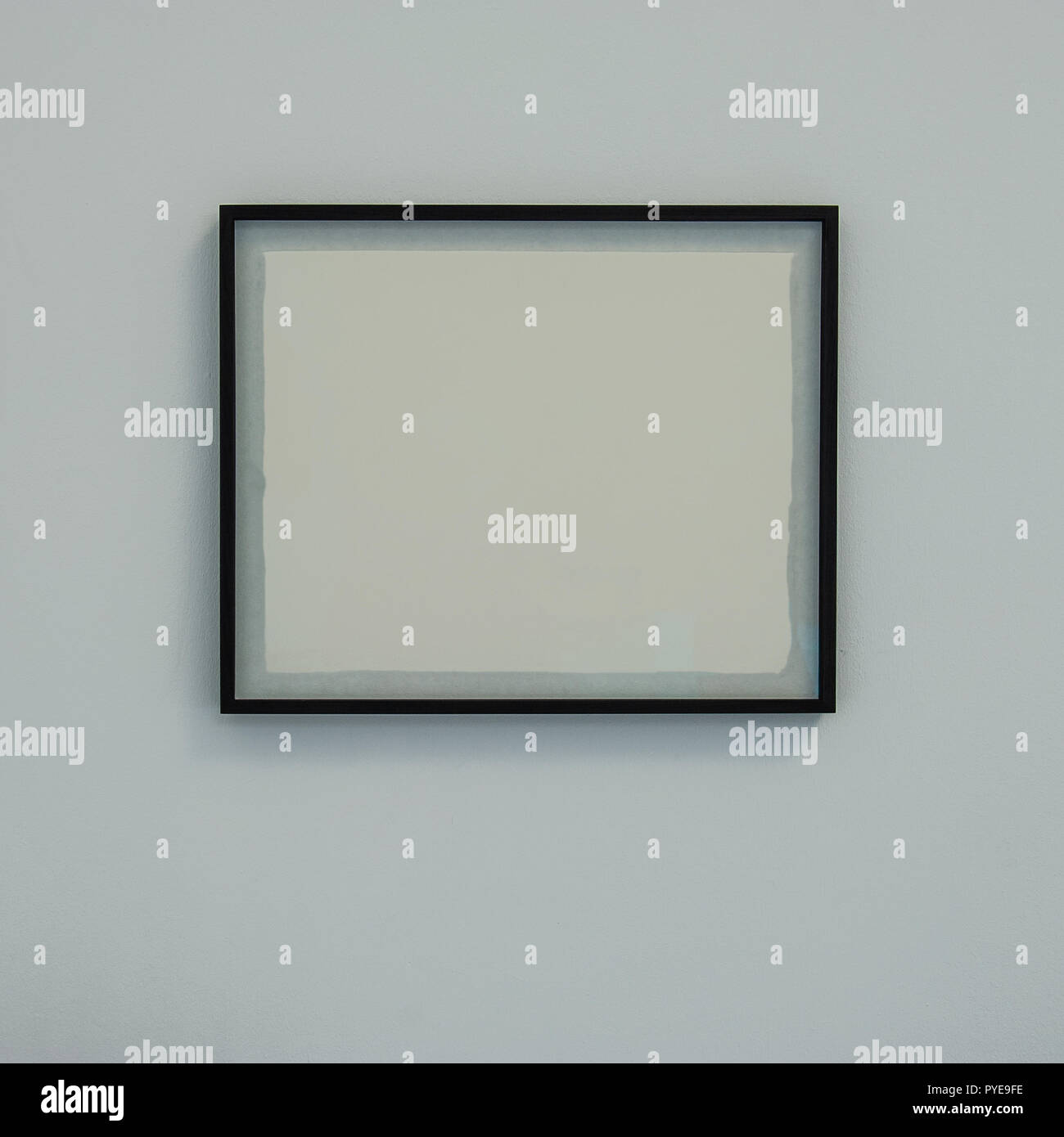 baguette frame with a white blank sheet on the wall. For web design. - Stock Image