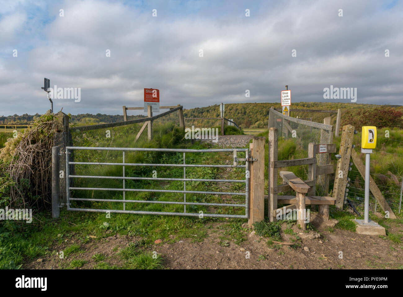 a user worked or pedestrian footpath crossing over the railway near Arundel on the south downs. - Stock Image