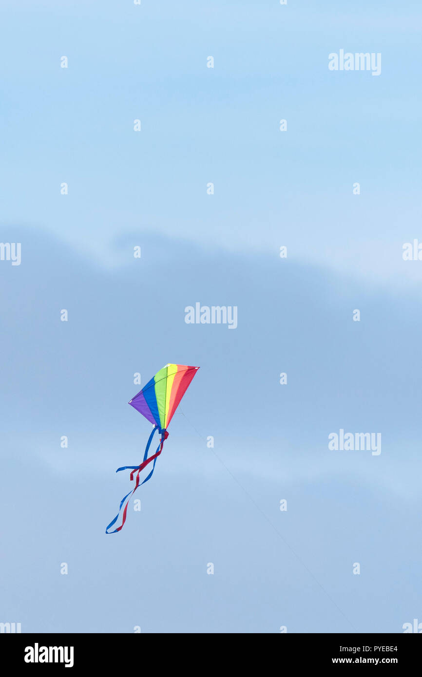 A multi coloured kite flying against a blue sky. - Stock Image