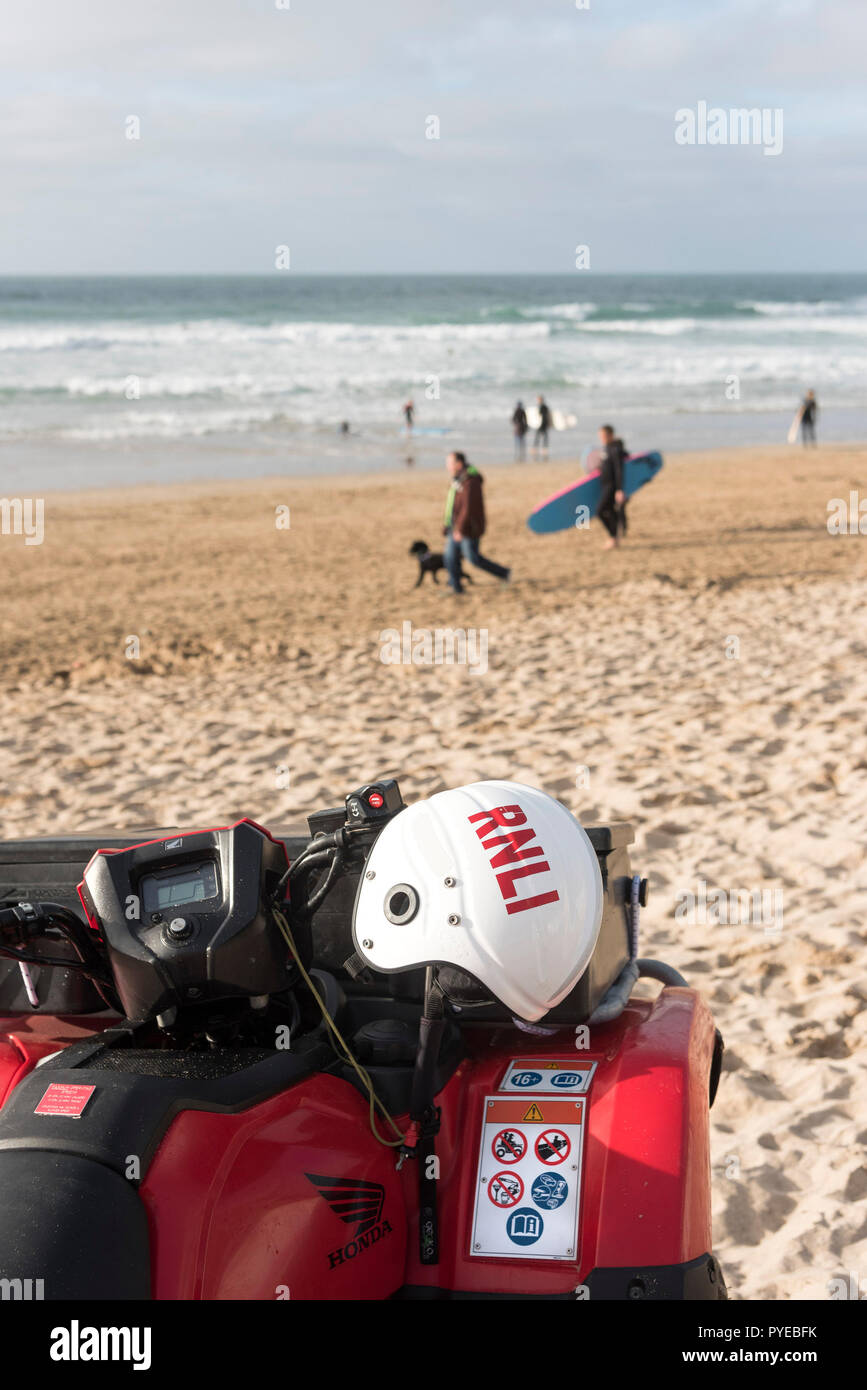 A RNLI safety helmet on the handlebars of a quad bike parked on Fistral Beach in Newquay in Cornwall. - Stock Image