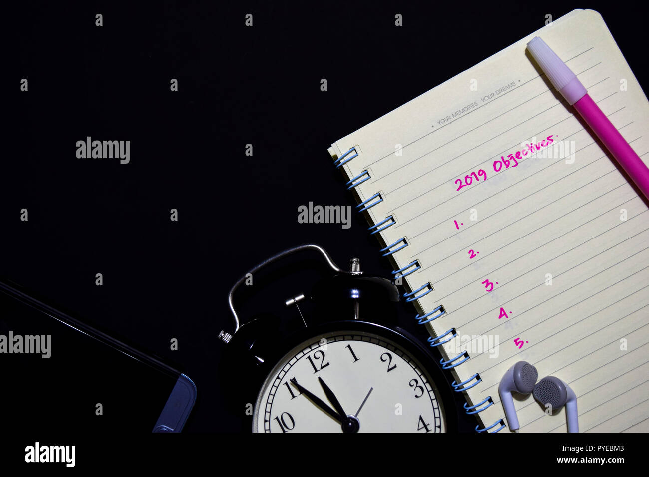 2019 Objectives text on notebook, alarm clock, color pen, smartphone on black background, for business presentation mock up for adding your list - Stock Image