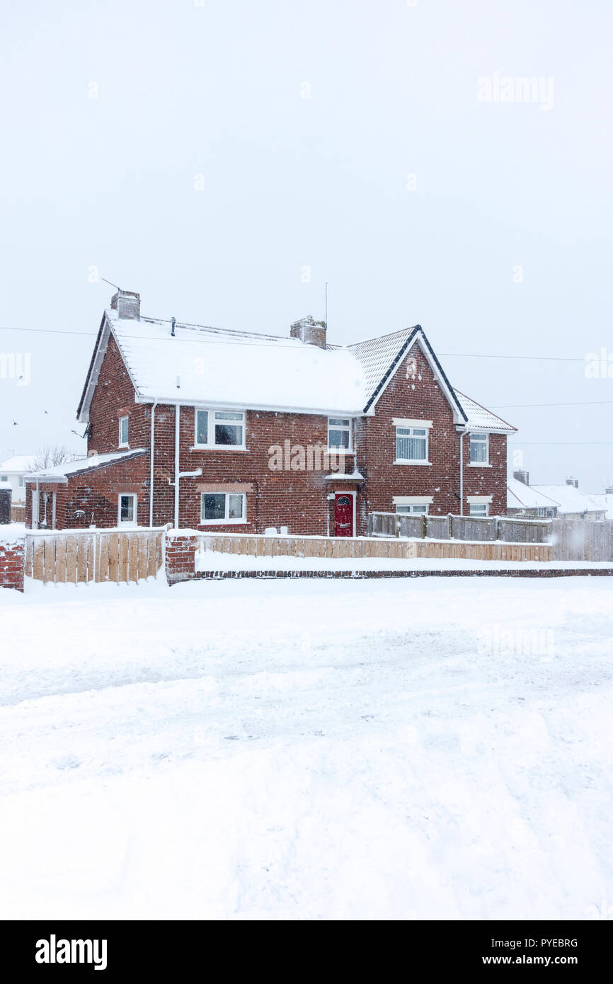 Two brick semi detached houses covered by a heavy fall of snow,  Consett, County Durham, England, UK - Stock Image
