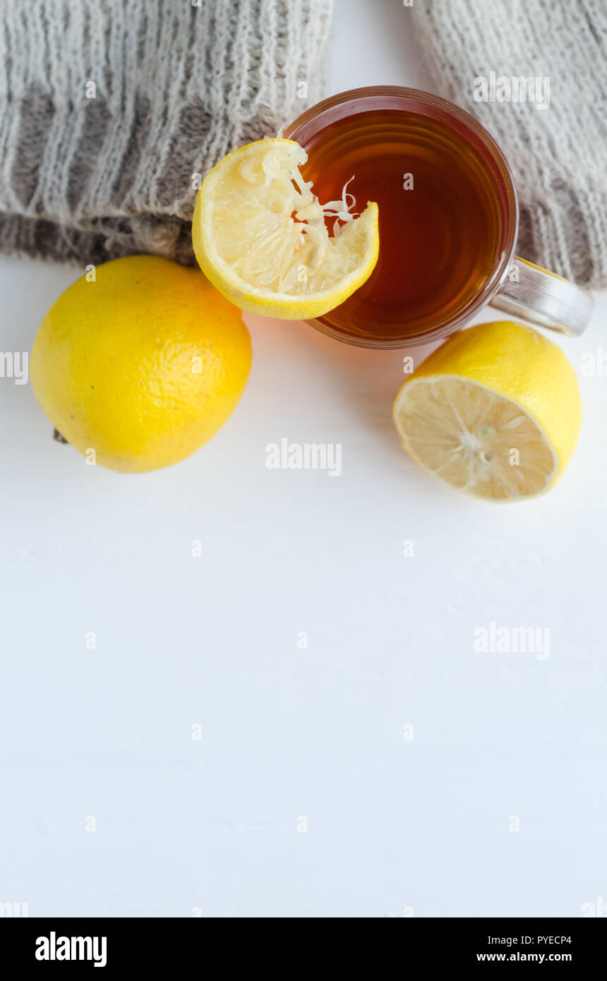 cup of tea with lemon , one and half lemon and woolen sweater. - Stock Image