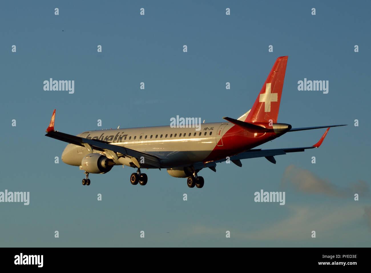 Helvetic Airways Embraer ERJ-190LR landing at London City Airport at  sunset - Stock Image
