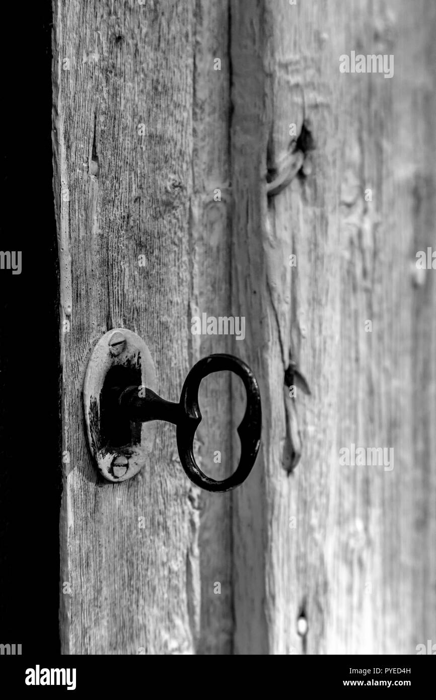 Rustic black iron skeleton key and door lock in an old Swedish farm in northern Sweden - Stock Image
