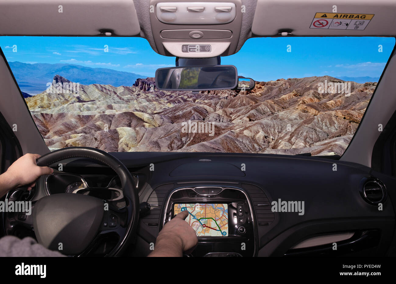 Driving a car while using the touch screen of a GPS navigation system towards Zabriskie Point, scenic place in Death Valley, California, USA - Stock Image