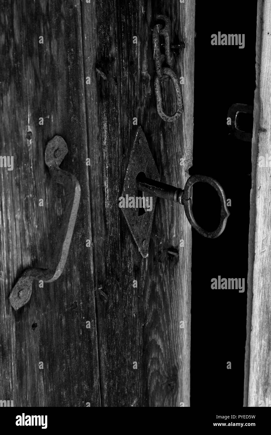 Rustic black iron skeleton key and door lock and handle in an old Swedish farm in northern Sweden - Stock Image