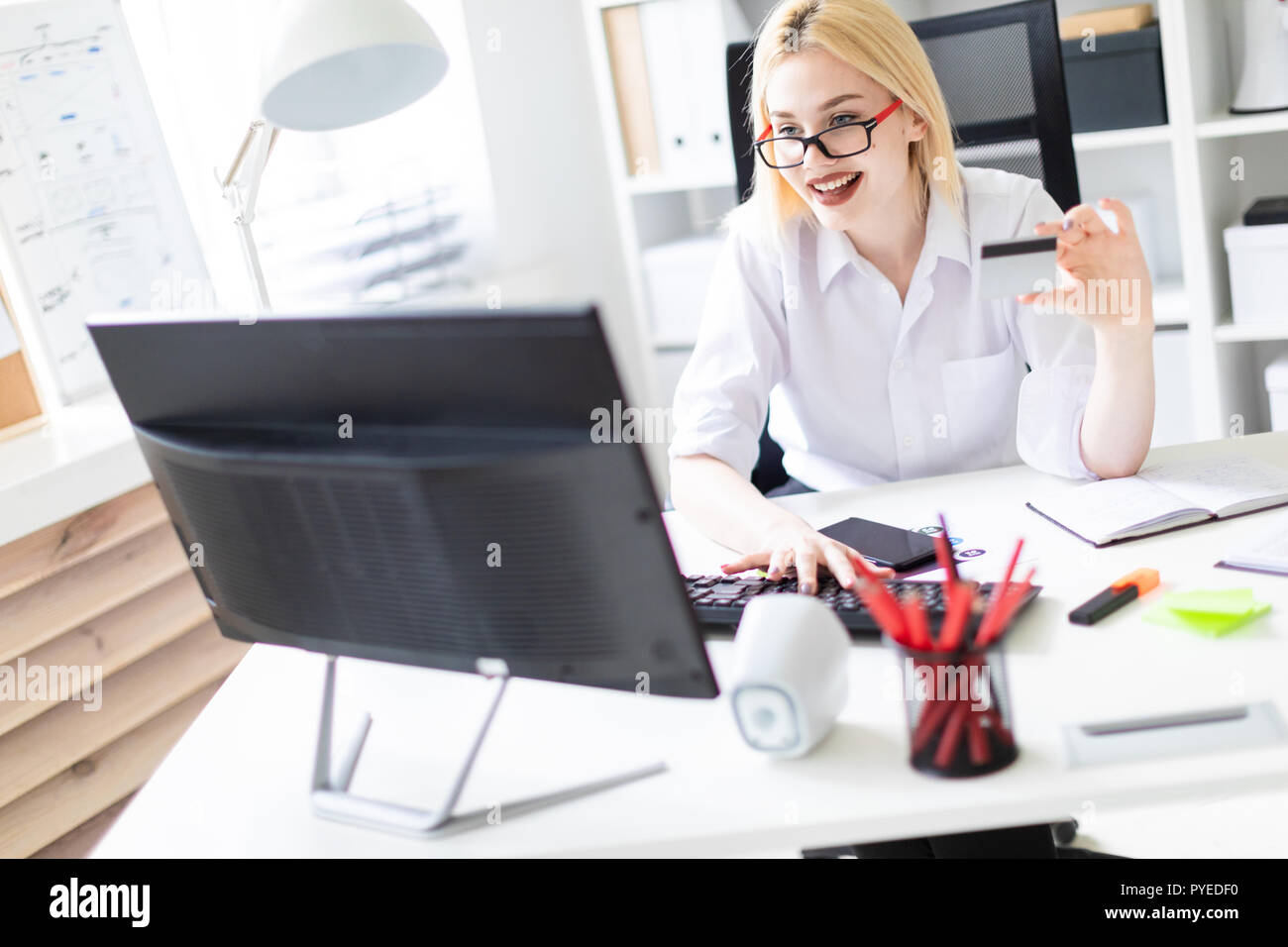 A young girl sitting in the office and holding a Bank card. - Stock Image